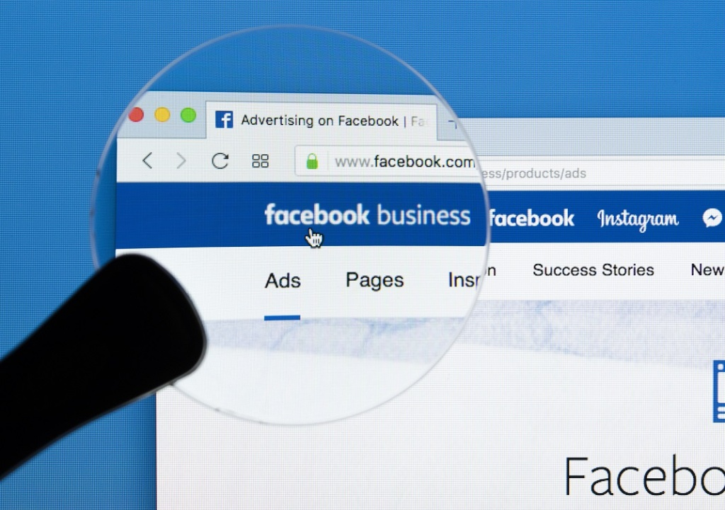 Sankt-Petersburg Russia December 7, 2017: Facebook business homepage website on Apple iMac monitor screen under magnifying glass. Facebook is the most popular social network in the world.