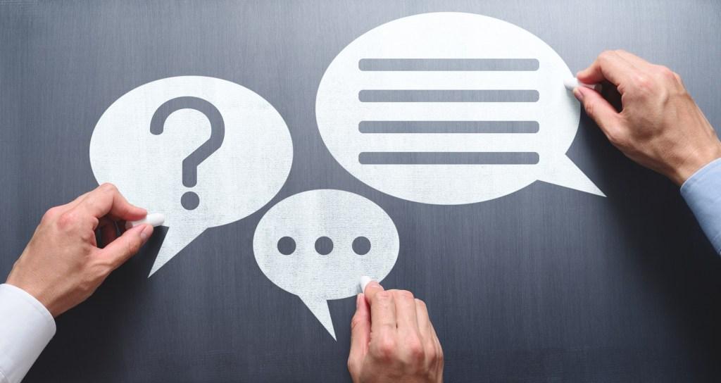 Business communication breakdown concept. Lack of communication skills. Businessmen drawing speech balloons on chalkboard.